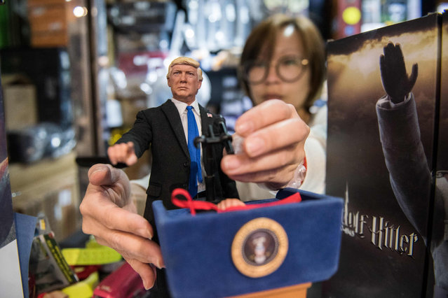 In this photograph taken on February 3, 2017, store manager Monita Chan adjusts the hand of a prototype figurine replica of US President Donald Trump, made by toymaker Dragon in Dream (DiD), next to a box containing a replica of Nazi leader Adolf Hitler (R) in Hong Kong toy shop Seven A Hong Kong doll maker with a history of creating figurines of controversial world leaders has launched a replica of US President Donald Trump complete with replaceable heads and hands. (Photo by Anthony Wallace/AFP Photo)