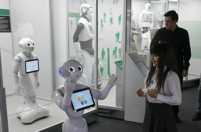 Charllotte Abbot reacts to the movement of Pepper an interactive French-Japanese robot, during a press preview for the Robots exhibition held at the Science Museum in London, Tuesday, February 7, 2017. (Photo by Alastair Grant/AP Photo)