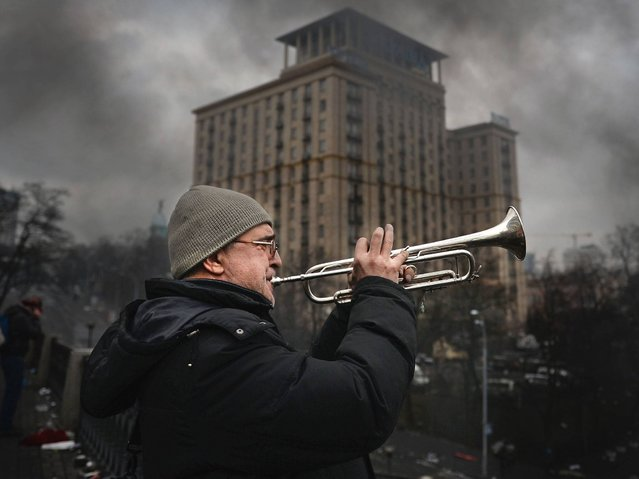 A man plays the trumpet as anti-government protesters continue to clash with police in Independence square in Kiev, on February 20, 2014. (Photo by Jeff J. Mitchell/Getty Images)