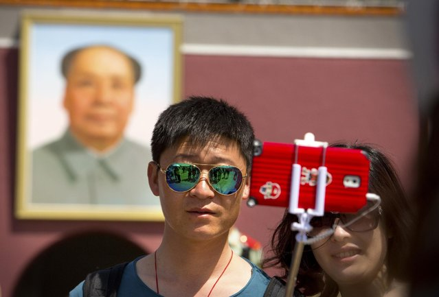 A tourist uses a selfie stick to take a photo of themselves in front of a large portrait of late Chinese leader Mao Zedong on the Gate of Heavenly Peace near Tiananmen Square in Beijing, Sunday, May 3, 2015. (Photo by Mark Schiefelbein/AP Photo)