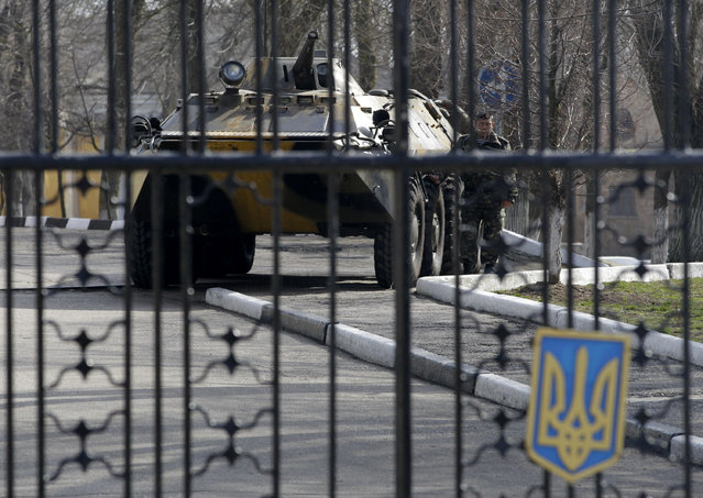 A Ukrainian armored personnel carrier is stationed behind the gate of a military base in the port of Kerch, Ukraine, Monday, March 3, 2014. (Photo by Darko Vojinovic/AP Photo)