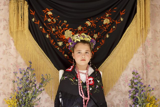 "A ""Maya"" girl sits in an altar during the traditional celebration of ""Las Mayas"" on the streets in Madrid, Spain Sunday, May 10, 2015. (Photo by Daniel Ochoa de Olza/AP Photo)"