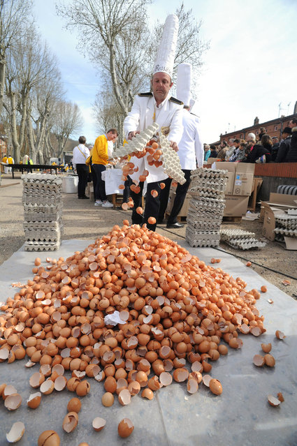 A member of the Giant Omelette Brotherhood of Bessieres dumps eggs shells in a pile during an event to make a giant omelette as part of Easter celebrations on March 28, 2016, on the main square of Bessieres, southern France. (Photo by Remy Gabalda/AFP Photo)