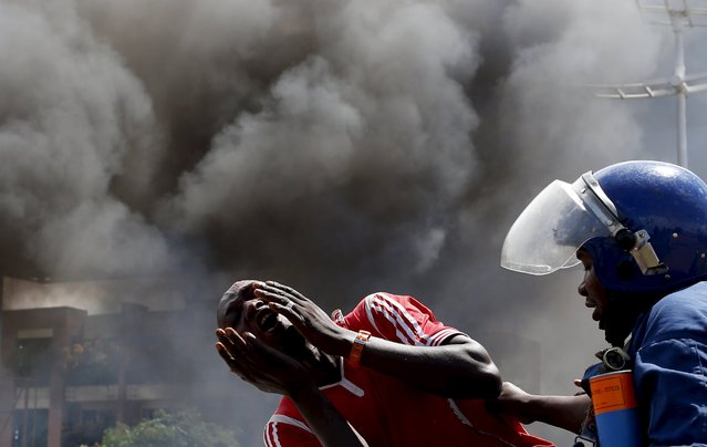 A detained protester cries in front of a burning barricade during a protest against President Pierre Nkurunziza's decision to run for a third term in Bujumbura, Burundi May 13, 2015. A Burundi army general said on Wednesday he had sacked Pierre Nkurunziza as president for seeking an unconstitutional third term in office, and was working with civil society groups to form a transitional government. (Photo by Goran Tomasevic/Reuters)