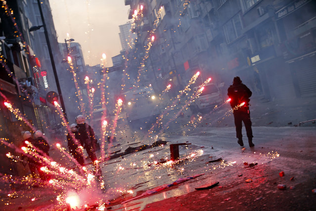 Fireworks thrown by anti-government protesters explode behind riot policemen near central Taksim square in Istanbul March 12, 2014. Turkish police fired tear gas and water cannon to push back thousands of demonstrators close to Istanbul's central Taksim square on Wednesday during a protest triggered by the death of a teenager wounded in street clashes last summer. (Photo by Murad Sezer/Reuters)