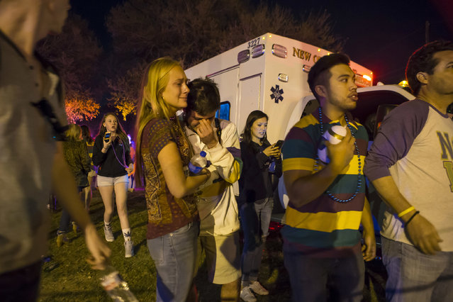 People hug and console each other as they watch New Orleans police work the scene where a vehicle plowed into a crowd injuring multiple people as the Krewe of Endymion parade rolled through New Orleans, Saturday, February 25, 2017. (Photo by Chris Granger/NOLA.com The Times-Picayune via AP Photo)
