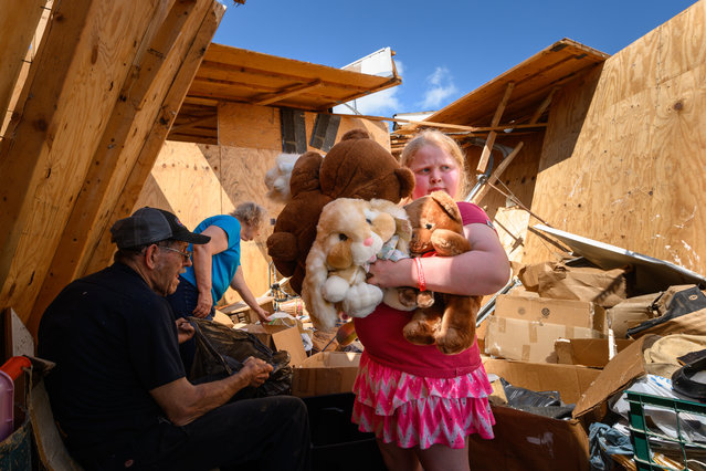 Nine-year-old Keeley Frank holds some stuffed animals her grandparents Al and Barb Scheidegger (at left) salvaged from their storage unit on May 23, 2019 in Jefferson City, Missouri. It was among many units destroyed by a tornado there on Thursday. A series of powerful tornadoes killed at least three people in southwestern Missouri causing extensive damage in Jefferson City, the state capital. (Photo by Reed Hoffmann/Getty Images)