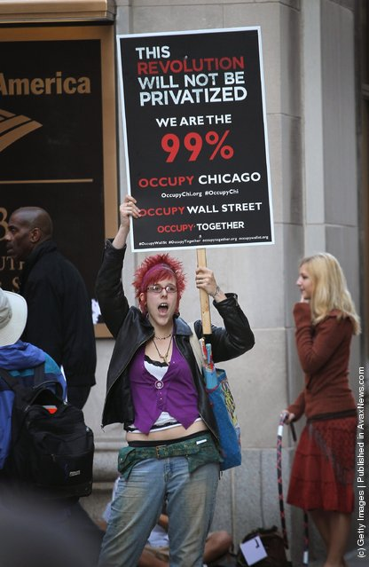A demonstrator with Occupy Chicago protests outside the Bank of America building
