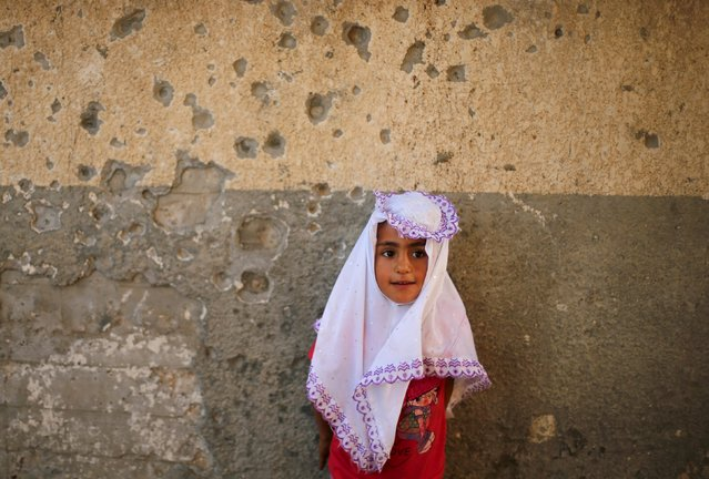A Palestinian girl poses for a photograph outside her family's house, that witnesses said was damaged by Israeli shelling during a 50-day war last summer, in Beit Lahiya town in the northern Gaza Strip May 20, 2015. (Photo by Mohammed Salem/Reuters)