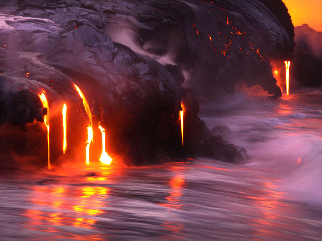 Two daredevil photographers have risked their lives to become the first people to capture the explosive moment fiery lava crashes into the sea – while in the water themselves. Fearless duo Nick Selway, 28, and pal CJ Kale, 35, brave baking hot 110F (43,3C) waters to snap the amazing images – standing just feet away from scalding heat and floating lava bombs. (Photo by Nick Selway/CJ Kale/Caters News Agency)