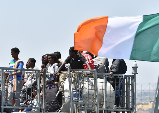 Migrants wait to be disembarked from the Irish Navy ship P31 L.E. Eithne at the Catania harbor, Italy, Tuesday, June 16, 2015. European Union nations failed to bridge differences Tuesday over an emergency plan to share the burden of the thousands of refugees crossing the Mediterranean, while on the French-Italian border, police in riot gear forcibly removed dozens of migrants. (AP Photo/Carmelo Imbesi)