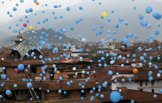Balloons dedicated to the memory of the people who died in April 25, 2015 massive earthquake are released into the sky at Basantapur Durbar Square in Kathmandu, Nepal, Saturday, June 27, 2015. (Photo by Niranjan Shrestha/AP Photo)