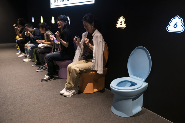 In this Monday, July 1, 2019, photo, visitors laugh as they jokingly motion to give a push while sitting on colorful toilet bowls at the Unko Museum in Yokohama, south of Tokyo. In a country known for its cult of cute, even poop is not an exception. A pop-up exhibition at the Unko Museum in the port city of Yokohama is all about unko, a Japanese word for poop. The poop installations there get their cutest makeovers. They come in the shape of soft cream, or cupcake toppingss. (Photo by Jae C. Hong/AP Photo)