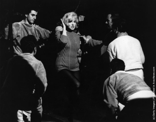 American actress Marilyn Monroe (1926  - 1962) talking to the Jack Cole dancers between takes on the set of the 20th Century Fox film Let's Make Love