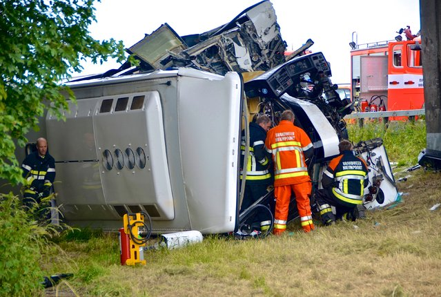Rescuers stand next to a British bus, which was transporting 34 children before it overturned and crashed on a motorway, near the city of Middelkerke, Belgium, June 28, 2015. A British bus with 34 children on board overturned and crashed on a motorway in Belgium on Sunday morning, killing a driver, a local mayor said. (Photo by Dominique Jauquet/Reuters)