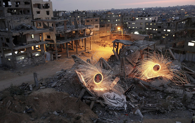 Palestinian guys light fireworks amid the rubble of destroyed Palestinian houses in Al Shejaeiya neighborhood, in the east of Gaza City, Gaza Strip, 28 June 2015. (Photo by Mohammed Saber/EPA)