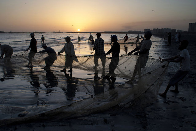 Pakistani fishermen pull their net out of the sea onto the beach in Karachi, Pakistan, Tuesday, April 8, 2014. (Photo by Shakil Adil/AP Photo)