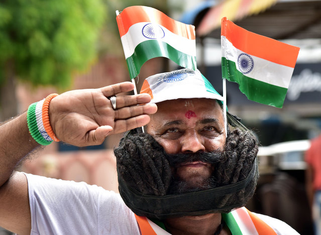 A man with his 28-feet (8.5m) long moustache, poses with national flags at Bikaner on August 13, 2019, as the country prepares to celebrate its 73rd anniversary of independence from British rule on August 15. (Photo by Dinesh Gupta/AFP Photo)