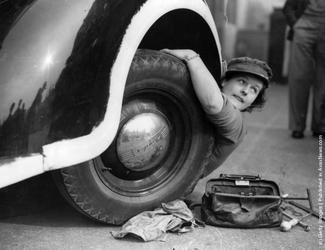 A member of the Mechanised Transport Training Corps changes a wheel at an ARP post in Lambeth, south London, 1939
