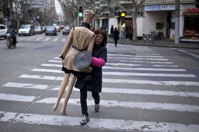 A woman carries a mannequin on a street in Shanghai March 26, 2013. (Photo by Aly Song/Reuters)