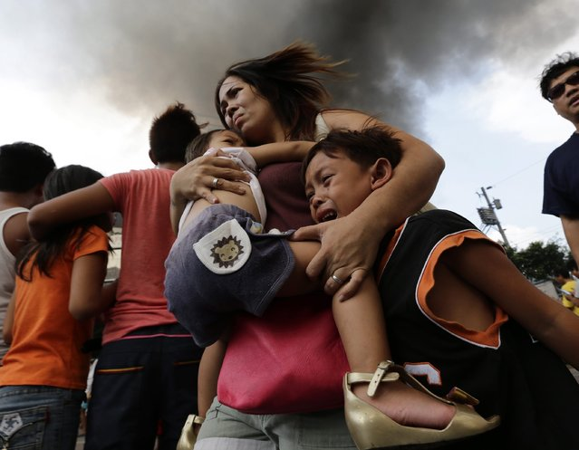 A Filipino mother carries her children while their house is on fire in a residential slum area in Manila, Philippines, 29 April 2014. The Manila Fire Department said fire left more than thirty families homeless and three residents were hurt. (Photo by Dennis M. Sabangan/EPA)