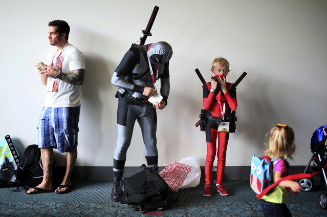 Attendees adjust their costumes at the 2015 Comic-Con International in San Diego, California, July 9, 2015. (Photo by Sandy Huffaker/Reuters)