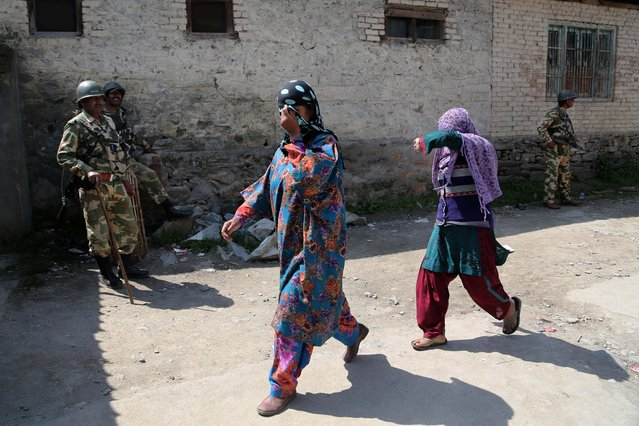 Kashmiri women hide their faces to conceal their identity as they come out of a polling station after casting their votes in Sheeri, about 60 kilometers (37 miles) north of Srinagar, India, Wednesday, May 7, 2014, following a call by rebels and separatists in the region to boycott the Indian parliamentary elections. Violence flared in Indian-controlled Kashmir on Wednesday as millions of Indians voted in the penultimate day of national elections. Rebels and separatists in the region have called for a boycott against the Indian parliamentary elections. (Photo by Dar Yasin/AP Photo)