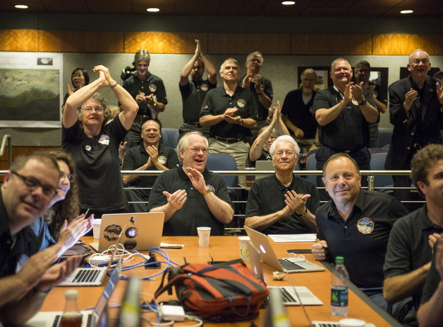 "Members of the New Horizons science team react to seeing the spacecraft's last and sharpest image of Pluto before closest approach later in the day at the Johns Hopkins University Applied Physics Laboratory (APL) in Laurel, Maryland July 14, 2015. The craft flew by the distant ""dwarf"" planet at 7:49 a.m. after reaching a region beyond Neptune called the Kuiper Belt that was discovered in 1992. The achievement is the culmination of a 50-year effort to explore the solar system. (Photo by Bill Ingalls/Reuters/NASA)"