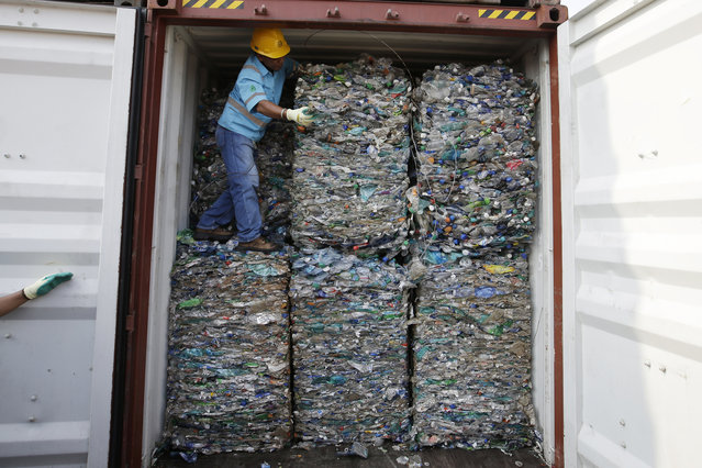 A worker stands inside a container full of plastic waste at Tanjung Priok port in Jakarta, Indonesia Wednesday, September 18, 2019. Indonesia is sending hundreds of containers of waste back to Western nations after finding they were contaminated with used plastic and hazardous materials. (Photo by Achmad Ibrahim/AP Photo)