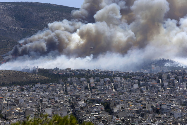 A helicopter flies over a fire on the mountain of Ymittos in the eastern suburbs of Athens on Friday, July 17, 2015. (Photo by Petros Karadjias/AP Photo)