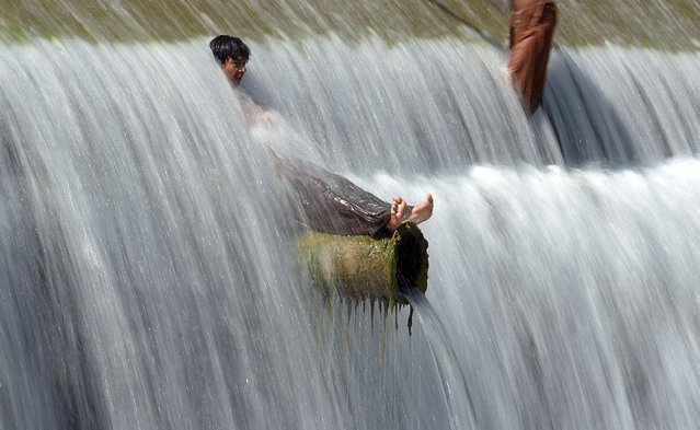 Pakistani youths cool off in a stream during hot weather on the outskirts of Islamabad on April 29, 2016. Pakistan's Meteorological Department has forecast hot and dry weather in most parts of the country with the highest temperatures recorded at 41 celsius in the southern Sindh province. (Photo by Aamir Qureshi/AFP Photo)
