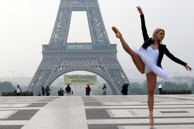 "A ballet dancer attends a photo shooting as activists from the environmentalist group Greenpeace unfurl a giant banner on the Eiffel Tower which reads ""Liberty, Equality, Fraternity"" in a call on French citizens to vote against the National Front (FN) presidential candidate Marine Le Pen, in Paris, France May 5, 2017. (Photo by Gonzalo Fuentes/Reuters)"