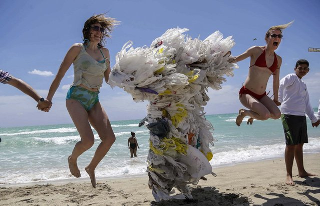 Rachel Bennett, of Brooklyn, N.Y., left, and Tiffany Threadgould, of Philadelphia, Pa., right, leap into the air as a friend takes their photograph, while joining hands with Steve Vincenti of Miami, center, who is covered with plastic shopping bags, during the Hands across the Sand protest in Miami Beach, Fla., on May 17, 2014. (Photo by Lynne Sladky/Associated Press)