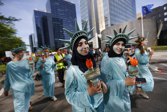 Protesters dressed as the Statue of Liberty march during a demonstration in the center of Brussels on Wednesday, May 24, 2017. Demonstrators marched in Brussels ahead of a visit of US President Donald Trump and a NATO heads of state summit which will take place on Thursday. (Photo by Peter Dejong/AP Photo)