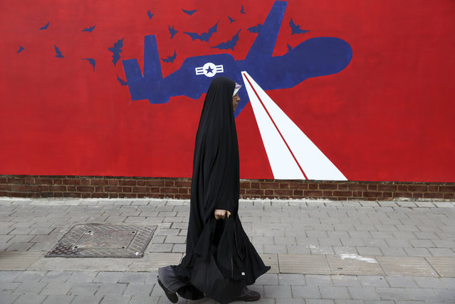 A woman walks past a new anti-U.S. mural on the wall of former U.S. embassy portraying the interception of Global Hawk US drone by Iran in Persian Gulf, after an unveiling ceremony in Tehran, Iran, Saturday, November 2, 2019. Anti-U.S. works of graphics is the main theme of the wall murals painted by a team of artists ahead of the 40th anniversary of the takeover of the U.S. diplomatic post by revolutionary students. (Photo by Vahid Salemi/AP Photo)