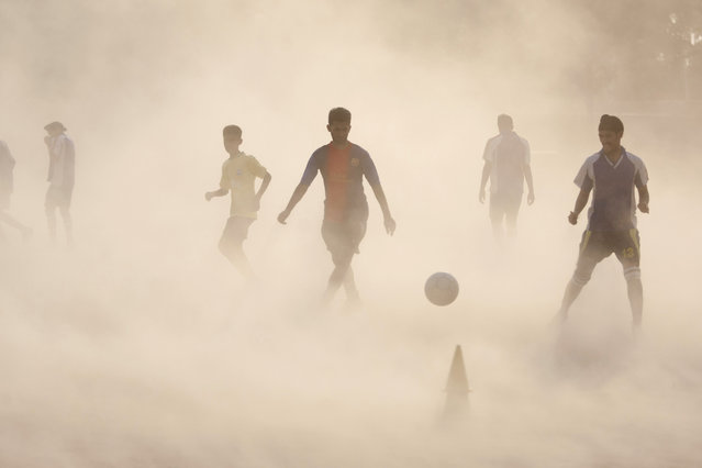 Aspiring young Indian soccer players continue with their practice during a dust storm in Jammu, India, Wednesday, June 11, 2014. (Photo by Channi Anand/AP Photo)