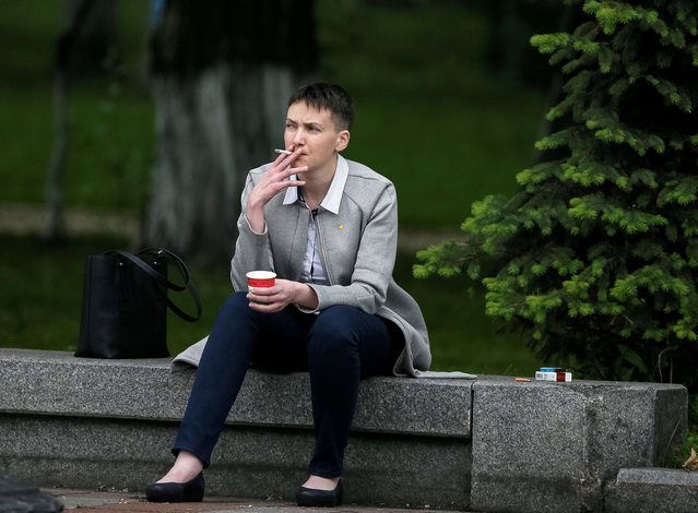 Ukrainian pilot and MP Nadiya Savchenko smokes and drinks a coffee near the parliament building before her first session in parliament after being freed from confinement in Russia as part of a prisoner swap in Kiev, Ukraine, May 31, 2016. (Photo by Gleb Garanich/Reuters)