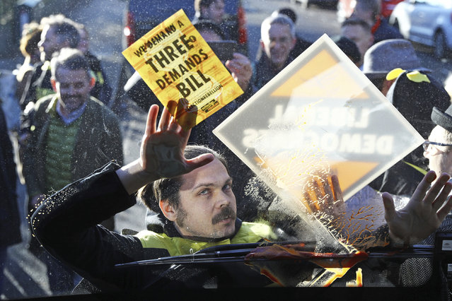 Environmental pressure group Extinction Rebellion protesters are dressed as bees and glue themselves to the front of Liberal Democrats Party bus carrying party leader Jo Swinson, during a visit to a youth centre in London, while on the General Election campaign trail, Wednesday December 4, 2019. The UK goes to the polls in a General Election on Dec. 12. (Photo by Aaron Chown/PA Wire via AP Photo)