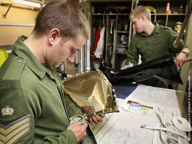 Lance Corporal of Horse Jeffrey Brown (L) polishes his ceremonial breast plate, known as a Cuirass, as his colleague Trooper Edward Spencer polishes one of his riding boots at The Household Cavalry Mounted Regiment (HCMR) at Hyde Park Barracks
