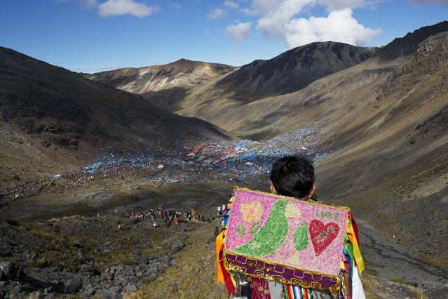 In this May 24, 2016 photo, a young boy descends the Qullqip'unqu mountain looking out at the tens of thousands of pilgrims gathered to celebrate the three-day festival Qoyllur Rit'i, translated from the Quechua language as Snow Star, in the Andean Sinakara Valley, in Peru's Cusco region. The celebration that mixes Catholic and indigenous beliefs honors Jesus as well as the area's glacier, which is considered sacred among some indigenous people. While the native celebration is far older, the Christian part of the ritual stretches back to the 1700s, when Jesus is said to have appeared to a young shepherd in the form of another boy. (Photo by Rodrigo Abd/AP Photo)