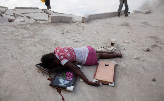 Fifteen-year-old Fabianne Geismar lies dead after being shot in the head after looting wall hangings from a destroyed store in Port-au-Prince, Haiti, January 19, 2010. (Photo by Carlos Garcia Rawlins/Reuters)