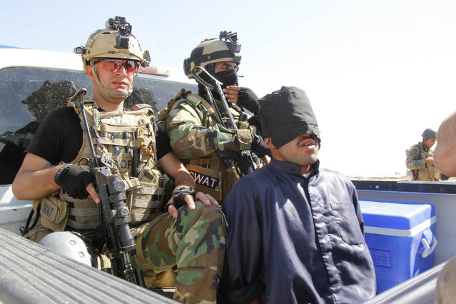 """Personnel from the Kurdish security forces detain a man suspected of being a militant belonging to the al Qaeda-linked Islamic State in Iraq and the Levant (ISIL) in the outskirts of Kirkuk June 16, 2014. Iraq's Shi'ite rulers defied Western calls on Tuesday to reach out to Sunnis to defuse the uprising in the north of the country, declaring a boycott of Iraq's main Sunni political bloc and accusing Sunni power Saudi Arabia of promoting """"genocide"""". (Photo by Ako Rasheed/Reuters)"""