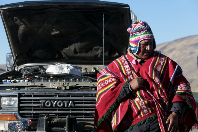 A witch doctor stands next to a car to bless it at 'La Cumbre' near La Paz, August 1, 2015. (Photo by David Mercado/Reuters)
