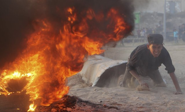 A Palestinian youth crawls near a fire during a military-style exercise at the Liberation Youths summer camp organised by the Hamas movement, in Rafah in the southern Gaza Strip August 1, 2015. (Photo by Ibraheem Abu Mustafa/Reuters)