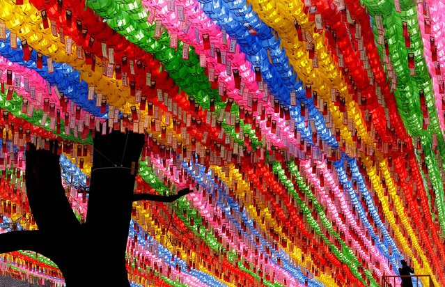 A worker attaches devotees' name tags with their wishes on lanterns in preparation for the birthday celebration of Buddha, which falls on May 28, at Jogye temple in Seoul, South Korea