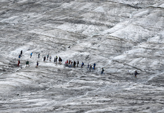 Tourists walk along a glacier during a simulated Mars mission on Tyrolean glaciers in Kaunertal August 7, 2015. (Photo by Dominic Ebenbichler/Reuters)
