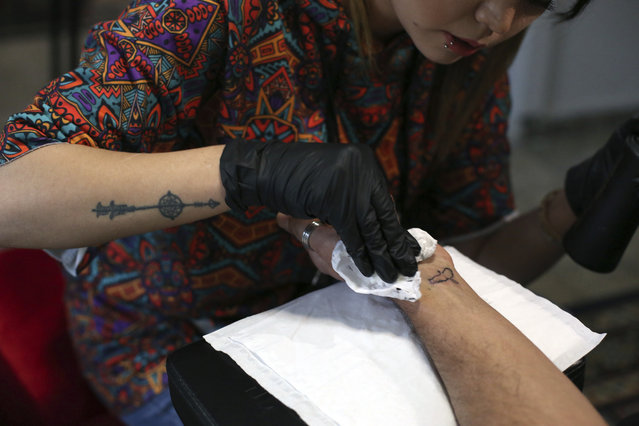 In this Saturday, December 9, 2019, photo, Suraya Shaheedi, 26, Tattoo artist, left, pierced tattoo to a male customer in Kabul, Afghanistan.  It's been 18 months since  Shaheedi started her mobile tattoo shop in the capital, Kabul. She's received death threats for taking on the taboo of the ink-on-skin drawings she does – as well as being a single woman willing to work with men. (Photo by Rahmat Gul/AP Photo)