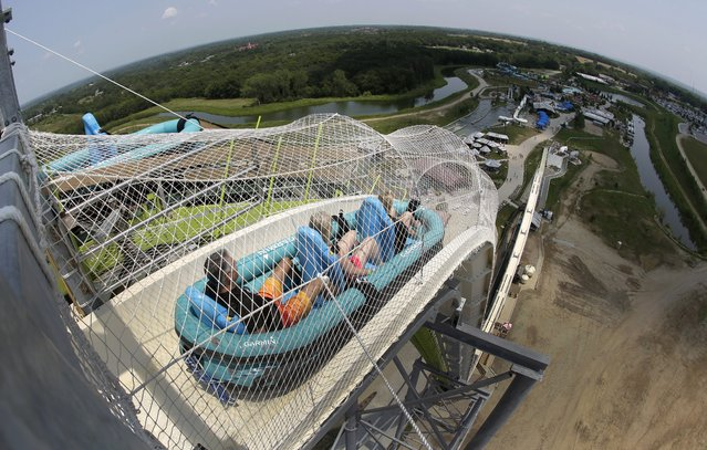 "In this photo taken with the fisheye lens, riders go down the world's tallest water slide called ""Verruckt"" at Schlitterbahn Waterpark, Wednesday, July 9, 2014, in Kansas City, Kan. The 168-foot-tall waterslide is scheduled to open to the public Thursday, after initially being slated to open May 23. (Photo by Charlie Riedel/AP Photo)"