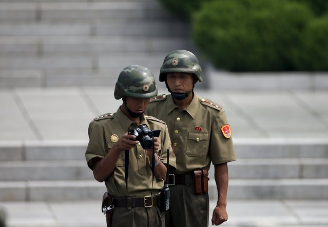 North Korean soldiers check their camera at the truce village of Panmunjom in the demilitarised zone (DMZ) separating the two Koreas, South Korea, August 11, 2015. (Photo by Kim Hong-Ji/Reuters)