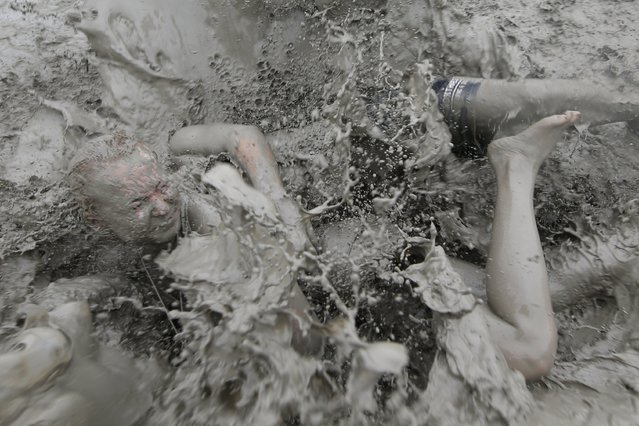 Festival-goers take a bath in a mud pool during the 20th Boryeong Mud Festival on Daecheon beach in Boryeong City, some 190 kilometers west of Seoul, South Korea, 22 July 2017. Tourists flock to the area to experience the beneficial properties of the Boryeong mud, as well as for a variety of entertainment events. The festival runs from 21 until 30 July. (Photo by Jeon Heon-Kyun/EPA/EFE)